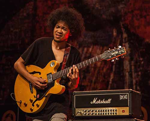 Guitarist-with-Afro-on-Stage-with-Semi-Hollow-Electric-Guitar