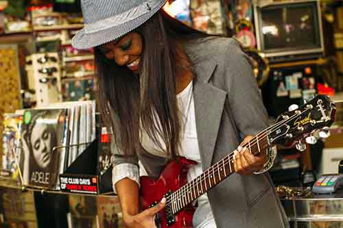 Woman-Checking-Out-Red-Guitar