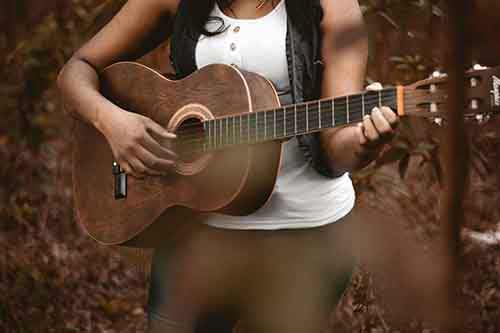 Woman-Holding-Acoustic-Guitar-in-Woods